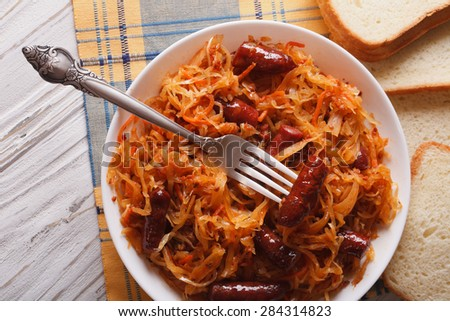 braised sauerkraut with sausages close-up in white plate. horizontal view from above - stock photo