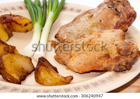 Braised steaks served with young potatoes and young onions. - stock photo