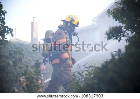 BRAMPTON, ONTARIO -  JULY 20 2012 - Firefighter walks through the backyard as fellow firefighters try to douse a house fire burning at 20 Esker Drive in Brampton Ontario on July 20, 2012 - stock photo