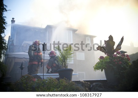 BRAMPTON, ONTARIO -  JULY 20 2012 - Firefighters working to douse a house fire burning at 20 Esker Drive in Brampton Ontario on July 20, 2012 - stock photo