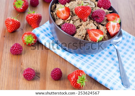 Bran flakes with fresh raspberries and strawberries on blue checkered cloth. Healthy eating choice concept - stock photo