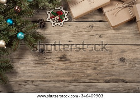 Branch of a Christmas tree with toys and Christmas gifts on wooden surface. Christmas background with decorations on wooden board. Copy space. Top view. Rustic style - stock photo