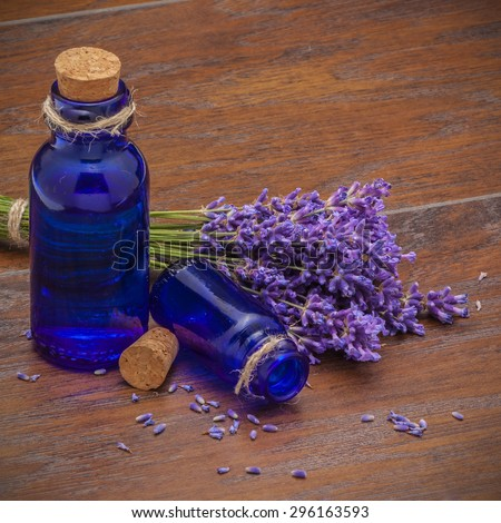 Branch of a lavender and vintage bottles on a wooden background. vignettes - stock photo