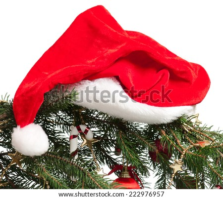 Branch of Christmas spruce with Santa claus red hat over white - stock photo
