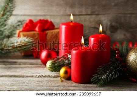 Branch of Christmas tree with balls and candles on grey wooden background - stock photo