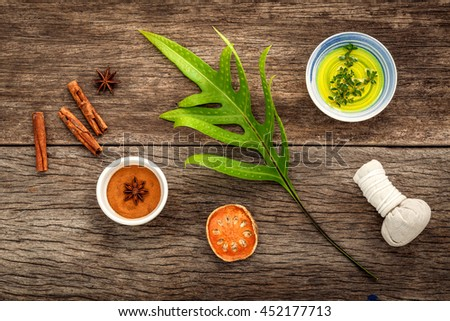 Branch of fern leaves with nature spa ingredients dried indian bael ,herbal compress ball,turmeric,cinnamon powder ,cinnamon sticks ,aromatic oil  and star anise on rustic background. - stock photo