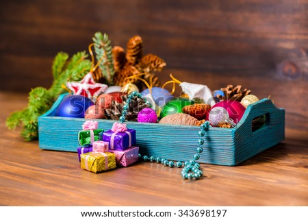 branch of fir tree and vintage wooden box with Christmas decoration, tinsel,  pinecones, stars, balls and gifts on wooden background, closeup - stock photo