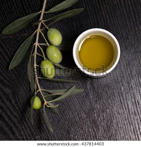 Branch of olive tree with green olive berries and cap of fresh olive oil on a black wooden table or board. - stock photo
