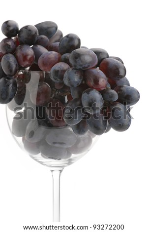 Branch of purple grape in wineglass on white background. - stock photo