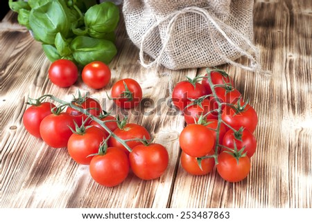 Branch of red ripe cherry tomatoes on  wooden board - stock photo
