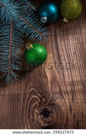 branches of fir tree and christmas baubles on vintage wood board. - stock photo
