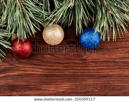 Branches of pine with Christmas toys on a wooden table - stock photo