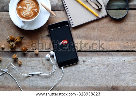 Brand new Apple iPhone 6 plus with YouTube app on the screen lying on old wood desk with headphones. YouTube is the popular online video sharing website. CHIANG MAI,THAILAND - OCT 19,2015 - stock photo