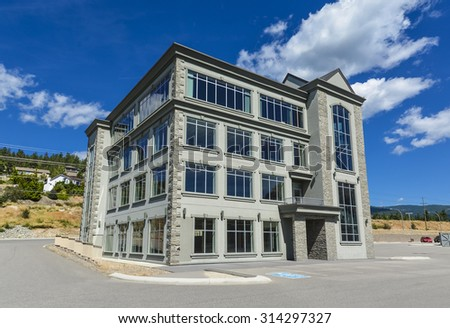 Brand new commercial building with retail and office space available for sale or lease. New office building with parking stalls in front and blue sky background awning opening. - stock photo
