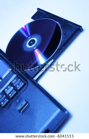 brand new laptop with cd in open cd drive, shot on white - stock photo