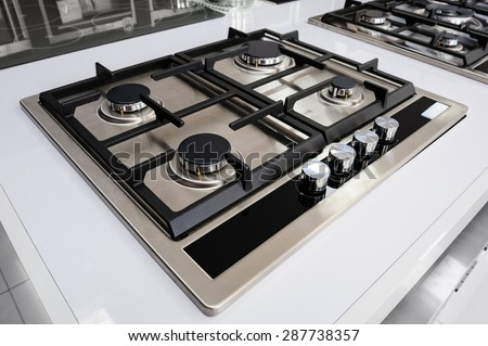 Brand new never used gas stove with stainless tray in appliance retail store - stock photo
