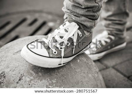 Brand new shoes, urban walking theme. Black and white photo with selective focus and shallow DOF - stock photo