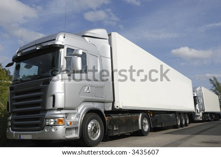 brand new trucks on line, silver-grey concept, no trademarks - stock photo