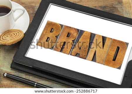 brand word in letterpress wood type printing blocks on a digital tablet with cup of coffee, - stock photo