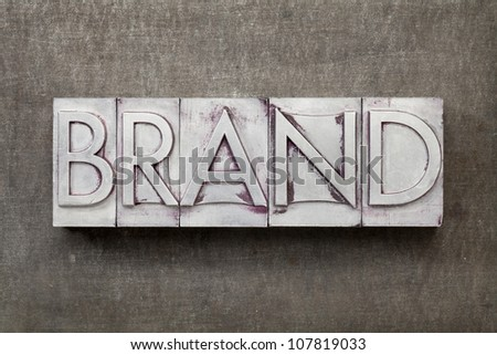 brand word in vintage letterpress metal type against a grunge steel sheet - stock photo