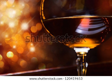 brandy for the maestro, snifter with brandy on a piano. - stock photo