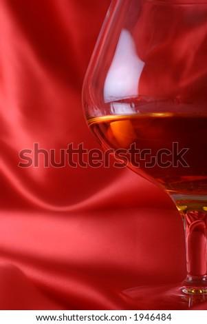 brandy glass on red silk background - stock photo