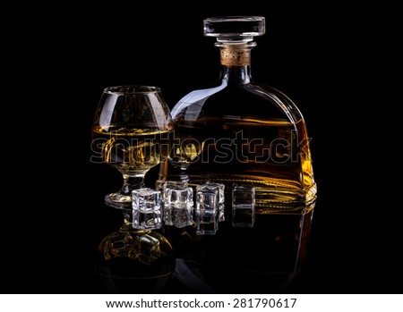 Brandy in large round glass and bottle - stock photo
