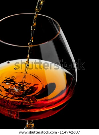 brandy or whiskey pouring into glass - stock photo