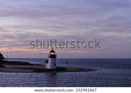 Brant Point Lighthouse during the blue hour just after sunset. Brant Point light, at the entrance to Nantucket Harbor, Cape Cod, Massachusetts, is the shortest lighthouse in New England. - stock photo