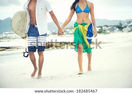 Brasil latino hispanic couple walking holding hands with surfboard and flag as sarong - stock photo