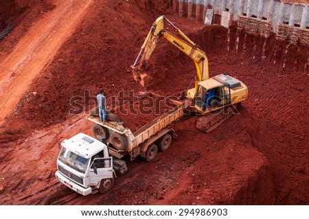 BRASILIA, BRAZIL - JUNE 6, 2015: Excavator loading dumper truck tipper in construction site of a new commercial building. - stock photo