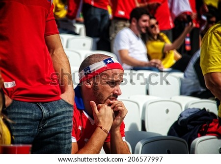 BRASILIA, BRAZIL - JUNE 23: Nervous Chilean fan biting his nails during a soccer game during the 2014 FIFA World Cup at Brasilias FIFA Fan Fest, on June 23, 2014. - stock photo