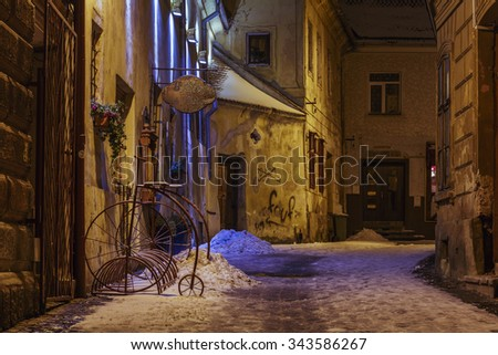 BRASOV, ROMANIA - 01 DECEMBER, 2014: Wintry night view of an empty backstreet with vintage bike parking rack in the historic center of Brasov, the 7th largest city and the most visited in Romania. - stock photo