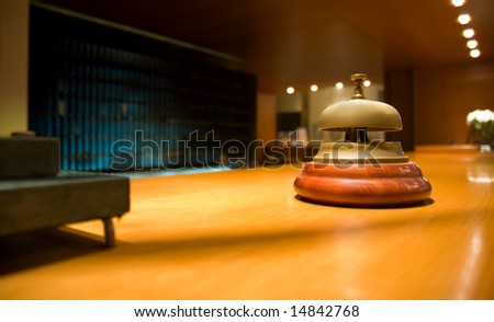 Brass bell on hotel reception (shallow dof) - stock photo