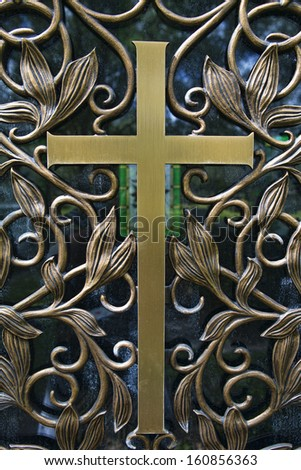 Brass Cross detail on the door of a mausoleum in a  Cemetery. Image shows detail of the metalwork on the door, with the stained glass window of the mausoleum in the background. - stock photo
