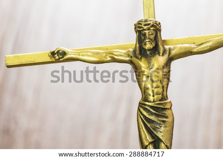 Brass  Cross with crucified Jesus Christ on wooden bur background, close up - stock photo