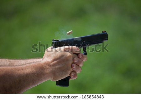 Brass flies from a semi automatic handgun that has just been fired - stock photo
