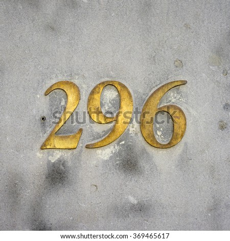brass house number two hundred and ninety six on a stone wall. - stock photo