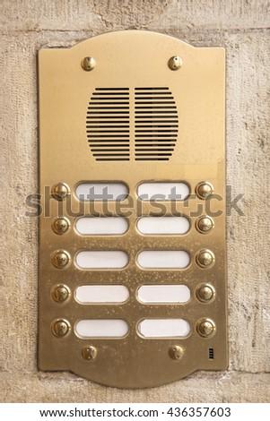Brass intercom on a marble facade - stock photo