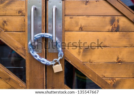 Brass iron lock and chain on wood door - stock photo