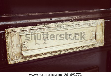 Brass letterbox slot  in old painted door, close-up, toned image - stock photo