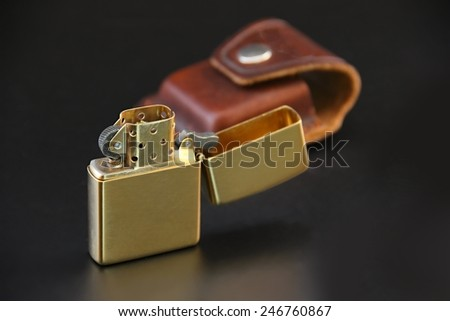Brass lighter and leather sheath on black background. - stock photo