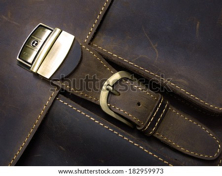 Brass metal clasp on old leather case with hand stitching - stock photo