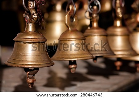 Brass praying bells hanging on old temple in Nepal  - stock photo