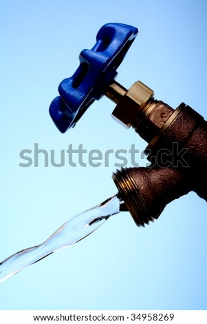 Brass water faucet with blue handle against blue background. - stock photo