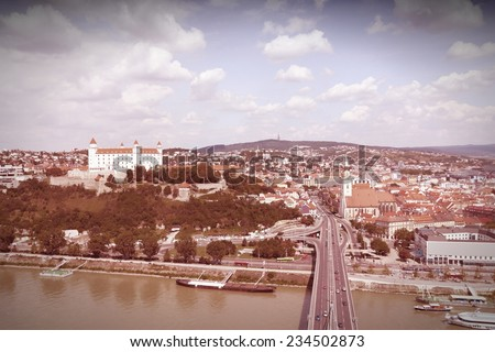 Bratislava, capital city of Slovakia. Cityscape with Danube river bridge, famous castle and old architecture. Cross processing color tone - filtered retro style. - stock photo