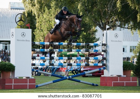 BRATISLAVA, SLOVAKIA - AUGUST 13: Philipp Zuger on horse Quarterback 4 jumps over hurdle during 6 bar competition at Grand Prix Bratislava on August 13, 2011 in Bratislava, Slovakia - stock photo