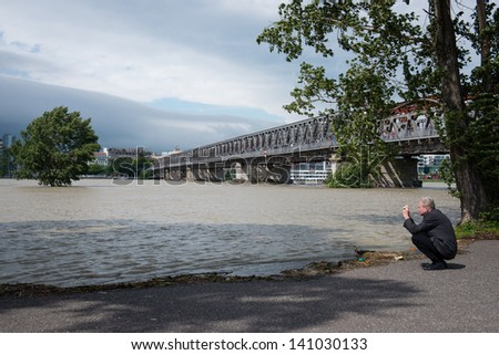 BRATISLAVA, SLOVAKIA - JUNE 4:  Man photograph as the water flooded Tyrsovo Embankment on the Petrzalka side of the Danube on June 4, 2013 in Bratislava - stock photo