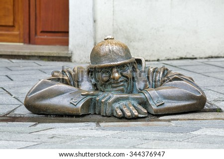 BRATISLAVA, SLOVAKIA - OCTOBER 11, 2015: Cumil the Peeper sculpture, also known as The Watcher or Man at Work. The sculpture by Viktor Hulik was unveiled on June 26, 1997 in the Old Town of Bratislava - stock photo