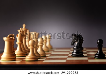 Brave black chess knight and pawn facing the entire army of white chess pieces on a wooden chessboard in focus - stock photo